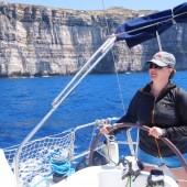 Kapitan za sterem, a w tle klify na Gozo..